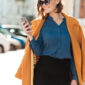 Smiling young woman in sunglasses and coat texting on mobile phone while walking on a street