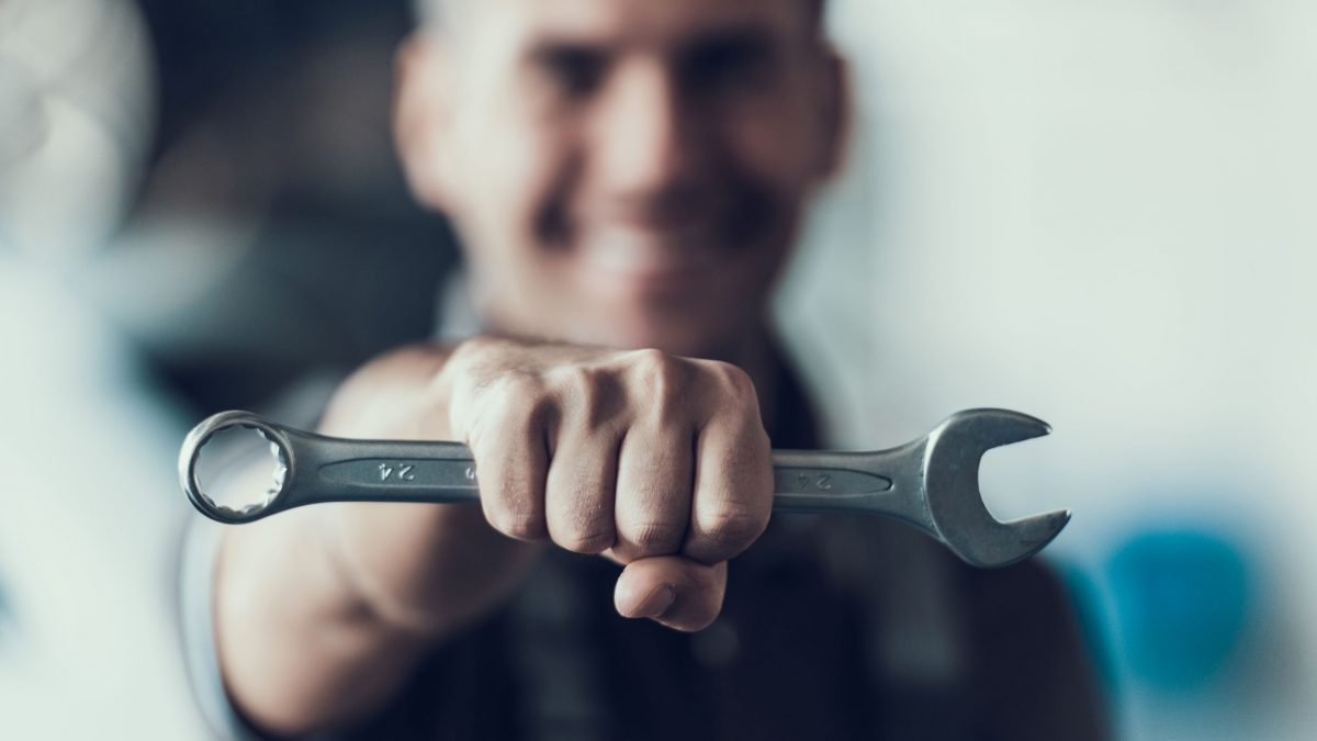 a mechanic, blurred in the background, holding a wrench